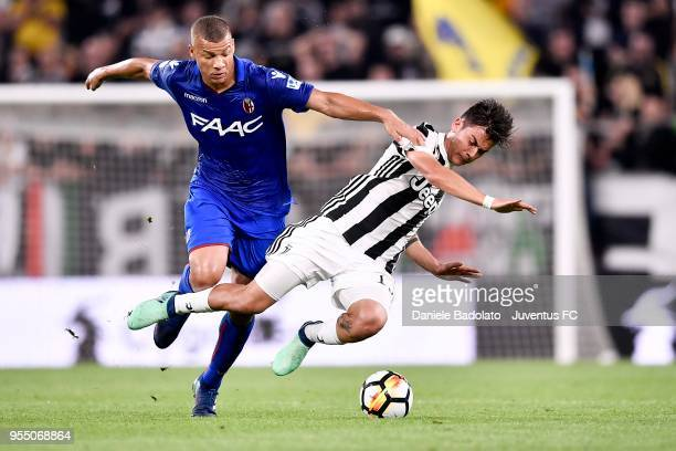 Paulo Dybala of Juventus competes for the ball with Sebastien De Maio of Bologna FC during the serie A match between Juventus and Bologna FC at...