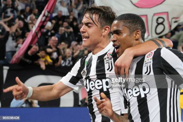 Paulo Dybala of Juventus FC celebrates with Douglas Costa after scoring the third goal of the Bianconeri during the Serie A football match between...