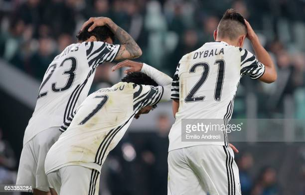 Paulo Dybala of Juventus FC celebrates with his teammates Daniel Alves da Silva and Juan Cuadrado after scoring the opening goal during the UEFA...
