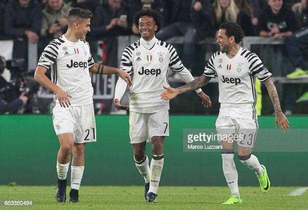 Paulo Dybala of Juventus FC celebrates with his teammates Juan Cuadrado and Daniel Alves da Silva after scoring the opening goal during the UEFA...