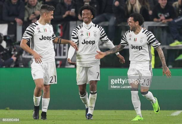 Paulo Dybala of Juventus FC celebrates with his teammates Juan Cuadrado and Daniel Alves da Silva after scoring the opening goal during the UEFA...