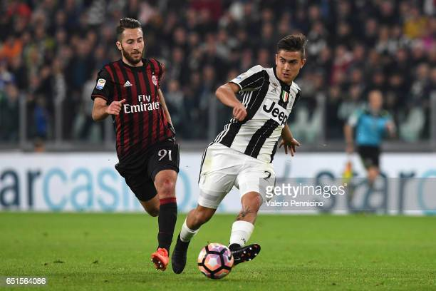 Paulo Dybala of Juventus FC in action against Andrea Bertolacci of AC Milan during the Serie A match between Juventus FC and AC Milan at Juventus...