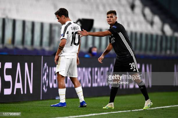 Paulo Dybala of Juventus FC looks dejected after suffering an injury as Bruno Guimaraes of Olympique Lyonnais consoles him during the UEFA Champions...