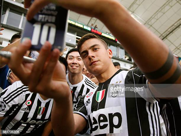 Paulo Dybala of Juventus FC signs for fans after the match between Juventus FC and South China of Hong Kong at Hong Kong Stadium on July 30 2016 in...