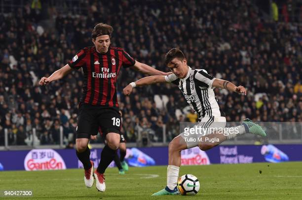 Paulo Dybala of Juventus holds off the challenge from Riccardo Montolivo of Milan during the serie A match between Juventus and AC Milan at Allianz...