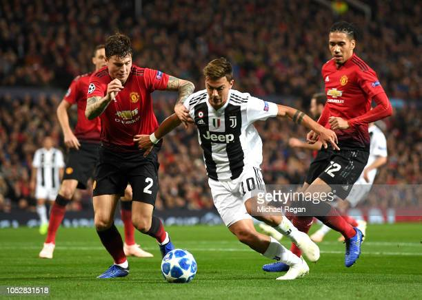 Paulo Dybala of Juventus holds off Victor Lindelof of Manchester United during the Group H match of the UEFA Champions League between Manchester...