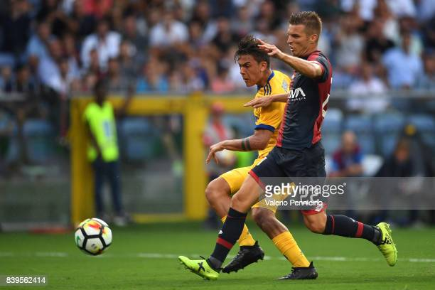 Paulo Dybala of Juventus is challenged by Darko Lazovic of Genoa CFC is challenged by during the Serie A match between Genoa CFC and Juventus at...