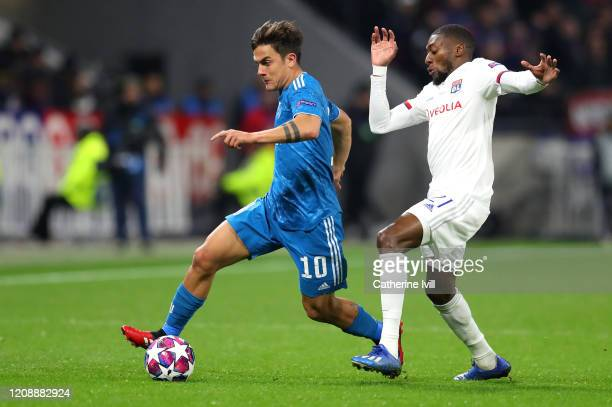Paulo Dybala of Juventus is challenged by Karl Toko Ekambi of Olympique Lyon during the UEFA Champions League round of 16 first leg match between...
