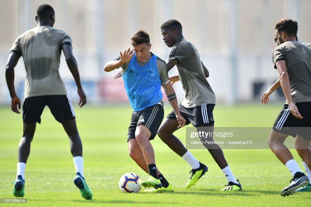 Paulo Dybala (C) of Juventus is challenged during a training session at JTC on August 5, 2018 in Turin, Italy.
