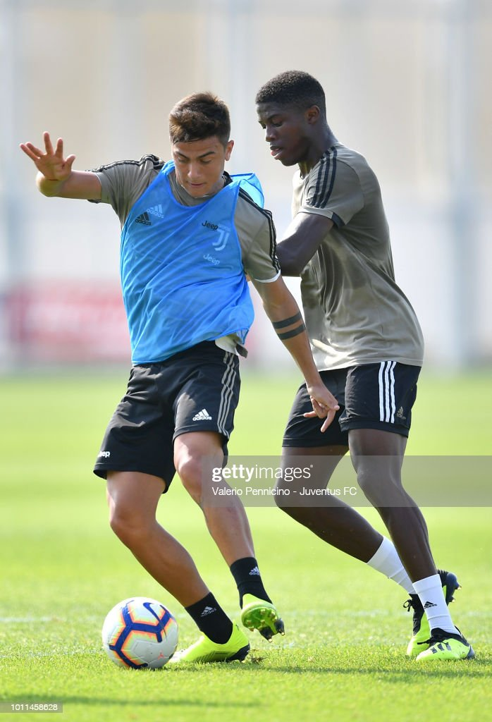 Paulo Dybala of Juventus is challenged during a training session at JTC on August 5, 2018 in Turin, Italy.