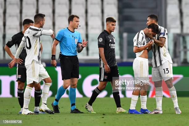 Paulo Dybala of Juventus is consoled by teammate Luiz Da Silva Danilo of Juventus after getting injured during the UEFA Champions League round of 16...