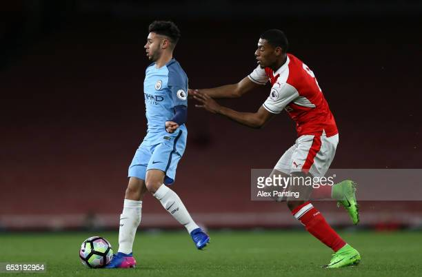 Paulo Fernandes of Manchester City is put under pressure by Jeff ReineAdelaide of Arsenal during the Premier League 2 match between Arsenal and...