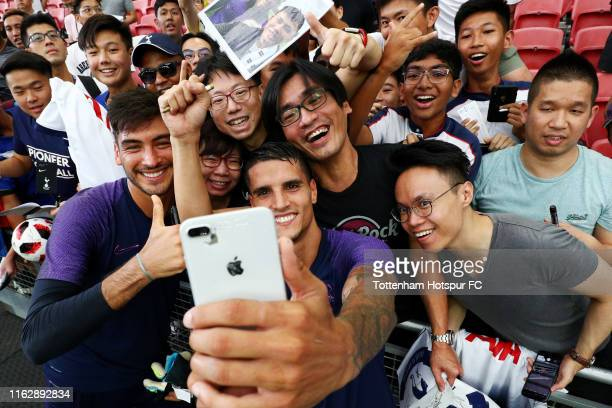 Paulo Gazzaniga and Erik Lamela pose for photos with fans during the Tottenham Hotspur official training/press conference at the Singapore National...