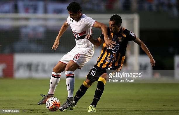 Paulo Henrique Ganso of Sao Paulo fights for the ball with Walter Veizaga of The Strongest during a match between Sao Paulo v The Strongest as part...