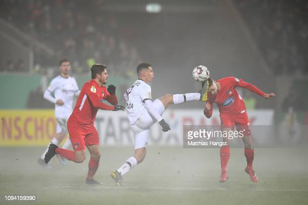 Paulo Henrique Sampaio Filho of Bayer 04 Leverkusen controls the ball as Maurice Multhaup of 1FC Heidenheim 1846 looks to head it during the DFB Cup...