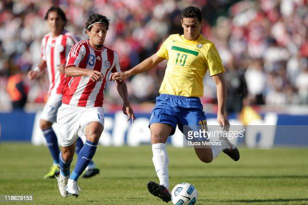 Paulo Henriqye Ganso of Brazil struggles for the ball with Enrique Vera of Paraguay during a match as part of Group B of Copa America 2011 at the...