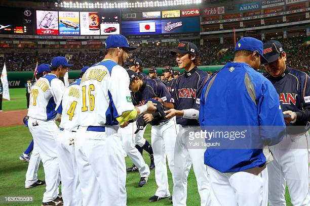 Paulo Orlando of Team Brazil exchanges team hats with Hayato Sakamoto of Team Japan before the Pool A Game 1 between Team Japan and Team Brazil...