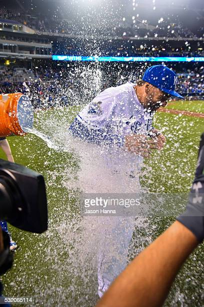 Paulo Orlando of the Kansas City Royals gets doused by a Gatorade bucket filled with water known as a 'Salvy Splash' by teammate Salvador Perez after...