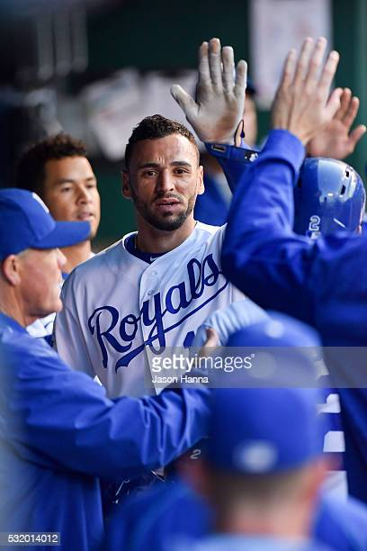Paulo Orlando of the Kansas City Royals high fives teammates in the dugout after scoring the Royals opening run of the game during the third inning...