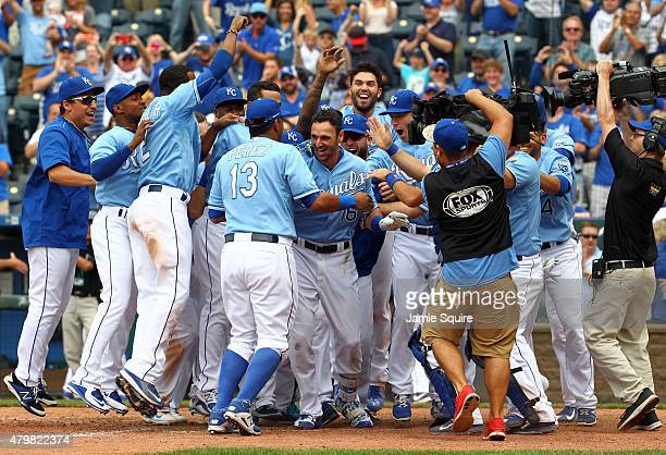 Paulo Orlando of the Kansas City Royals is congratulated by teammates at home plate after hitting a walk-off grand slam in the bottom of the 9th...