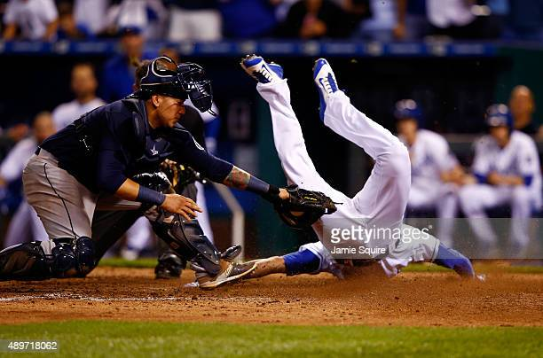 Paulo Orlando of the Kansas City Royals slides safely into home plate to score past catcher Jesus Sucre of the Seattle Mariners during the 10th...