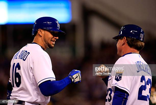 Paulo Orlando of the Kansas City Royals smiles is congratulated by third base coach Mike Jirschele as he arrives on third base after hitting a triple...
