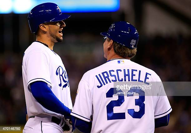 Paulo Orlando of the Kansas City Royals smiles toward third base coach Mike Jirschele as he arrives on third base after hitting a triple to drive in...