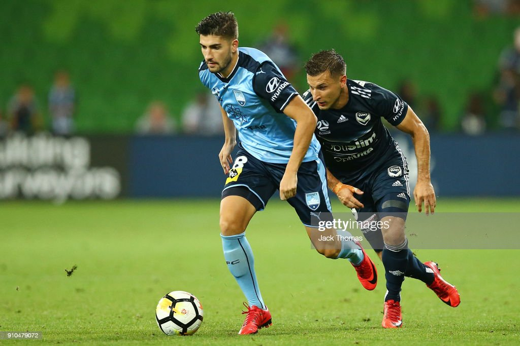 Paulo Retre of Sydney FC (L) compete for the ball against Kosta Barbarouses of the Victory during the round 18 A-League match between Melbourne Victory and Sydney FC at AAMI Park on January 26, 2018 in Melbourne, Australia.