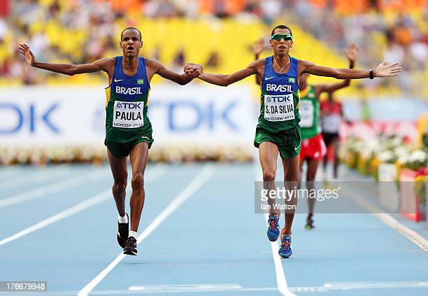 Paulo Roberto Paula of Brazil and Solonei da Silva of Brazil hold hands as they cross the finish line in the Men's Marathon during Day Eight of the...