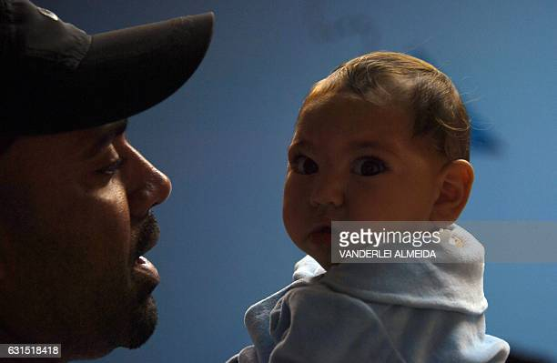 Paulo Sergio holds his sixmonthold baby Arthur Meneses as they wait for medical exams at the State Brain Institute in Rio de Janeiro Brazil on...