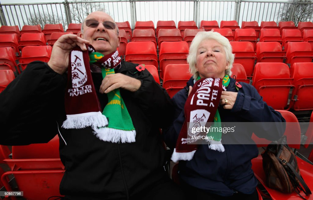 Paulton supporters Norman and Jean Weston adjust their football scarves as they pose for a photograph at Paulton Rovers Football Club on November 6, 2009 in Paulton, England. Non-league Paulton Rovers are currently preparing for the single biggest day in their 128-year history as they face Norwich City in the FA Cup first round tomorrow. The Somerset village club, which beat Chippenham Town before being drawn against the League One club, normally has an attendance of 200, but will see capacity at the ground swell to 2500 and the match broadcasted live on television to an estimated audience of 2 million.