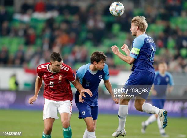 Paulus Arajuuri of Finland heads the ball in front of Sauli Vaisanen of Finland and Adam Szalai of Hungary during the UEFA Nations League group stage...