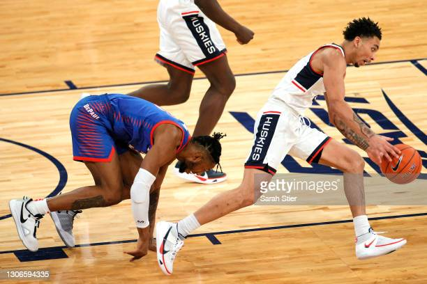 Pauly Paulicap of the DePaul Blue Demons trips battling James Bouknight of the Connecticut Huskies for a loose ball in the first half during the...