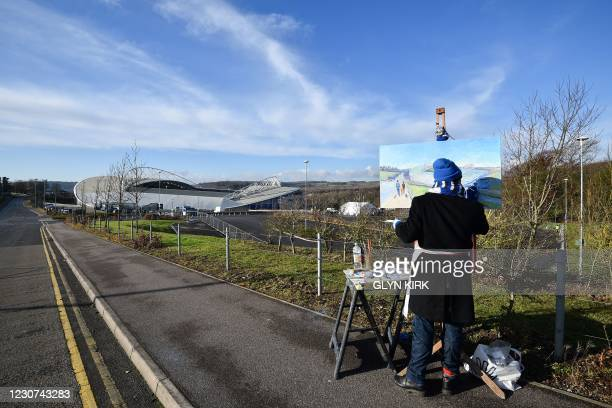 Pauly the painter works on his easel outside the stadium ahead of the English FA Cup fourth round football match between Brighton and Hove Albion and...