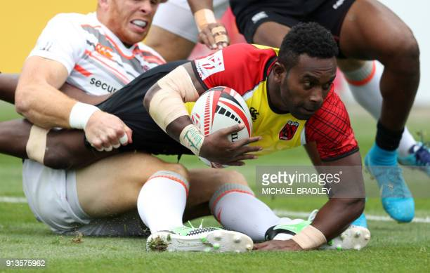 Paupa New Guinea's Wesley Vali is held up short of the try line by Englnad's James Rodwell during the World Rugby Sevens Series match between Paupa...