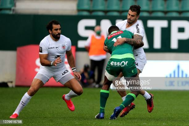 Pau's Fijian wing Aminiasi Tuimaba is tackled by Toulouse's French centre Sofiane Guitoune during the French TOP 14 rugby match Section Paloise vs...
