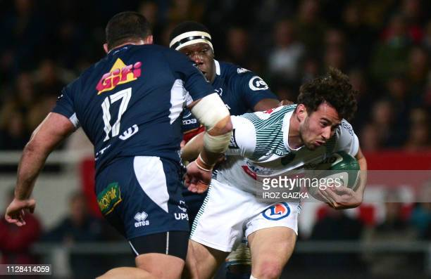 Pau's French flyhalf Antoine Hastoy is tackled during the French Top 14 rugby union match between Pau and Agen at the Hameau Stadium in Pau...