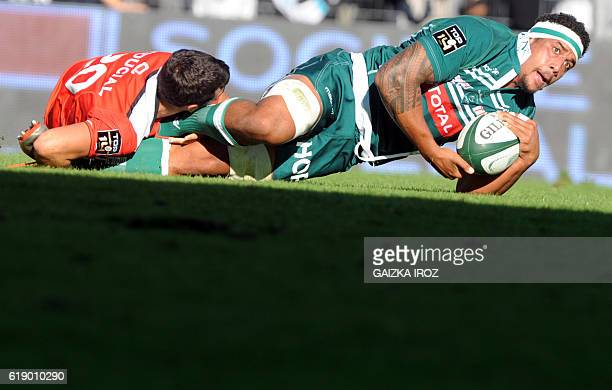 Pau's Samoan lock Masalosalo Tutaia is tackled by Pau's French scrumhalf Sebastien Bezy during the rugby union match between Section Paloise and...