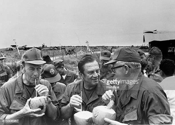 Pausing for refreshments during their visit to Huu Thanh a recently pacified village three US Senators on President Nixon's fact finding mission...
