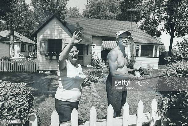 Pausing in their gardening Mr and Mrs Bob Milthorpe wave at Island visitors outside their home at 16 Lakeshore Ave Ward's Island I a casual tourist...