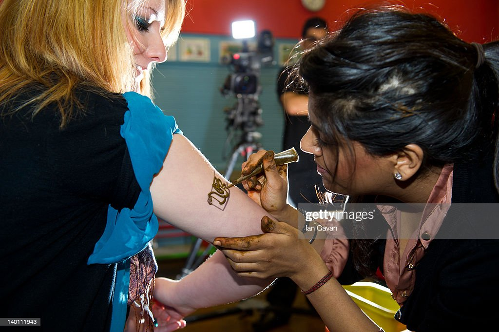 Pavan Ahluwalia Applies A Henna Mehndi Armband To A Member Of Staff