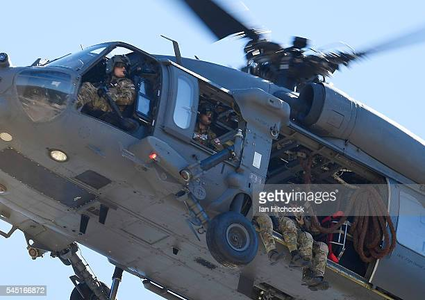 HH60 Pave Hawk helicopter flies over the site of a simulated IED stike on July 6 2016 in Townsville Australia Exercise Angel Reign is the largest Air...