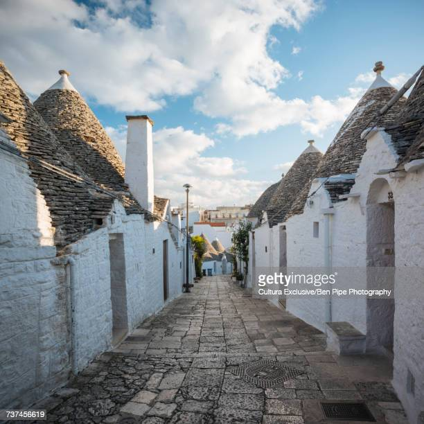 Paved alley with whitewashed trullo houses, Alberobello, Puglia, Italy