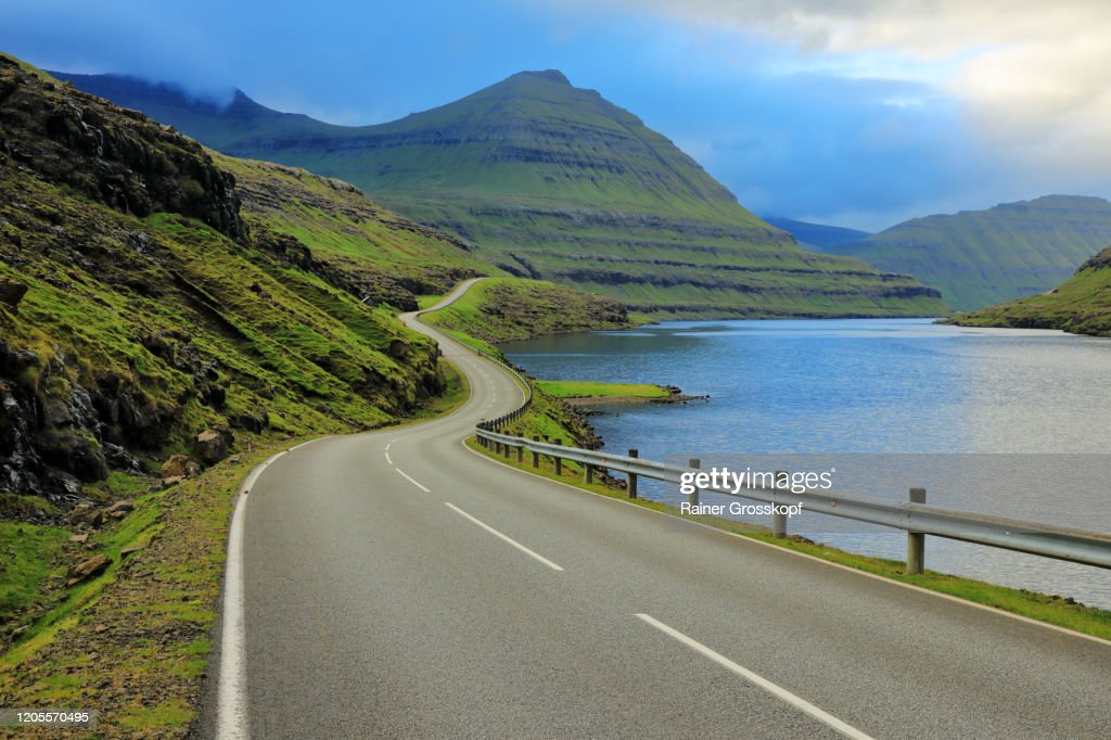 A paved road through grassy hills and mountains follows the shoreline of a fjord : Stock-Foto