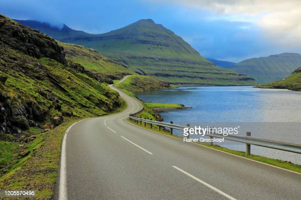 a paved road through grassy hills and mountains follows the shoreline of a fjord - rainer grosskopf stock-fotos und bilder