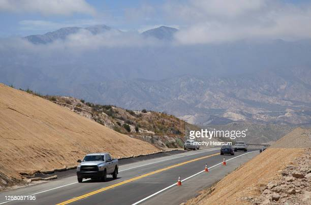paved road with four vehicles runs through a mountain pass; clouds, fog and blue sky beyond - timothy hearsum stock-fotos und bilder