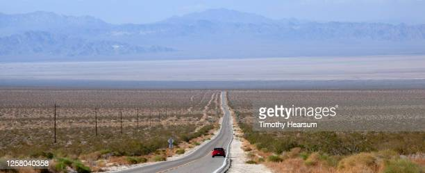 paved road with lone red car leads to the horizon; hazy mountain range and blue sky beyond - timothy hearsum stock pictures, royalty-free photos & images