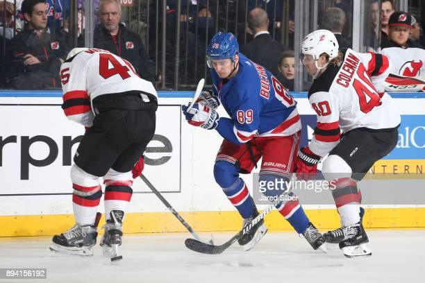 Pavel Buchnevich of the New York Rangers skates with the puck against Blake Coleman and Sami Vatanen of the New Jersey Devils at Madison Square...