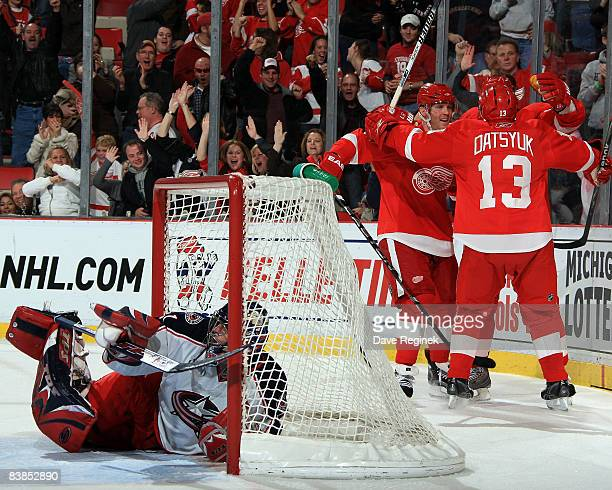 Pavel Datsyuk and Dan Cleary of the Detroit Red Wings celebrate with teammate Marian Hossa after he scores the game winning goal on Pascal Leclaire...