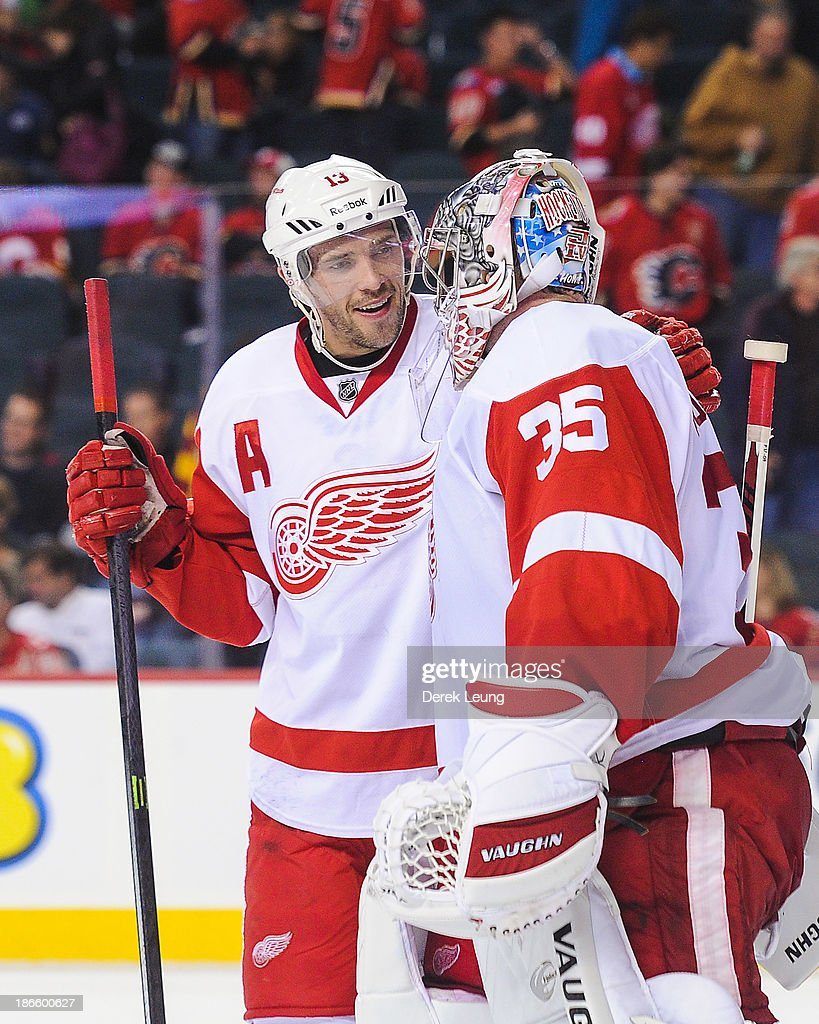 Pavel Datsyuk #13 and Jimmy Howard #35 of the Detroit Red Wings celebrate their victory over the Calgary Flames aftter an NHL game at Scotiabank Saddledome on November 1, 2013 in Calgary, Alberta, Canada. The Red Wings defeated the Flames 4-3.